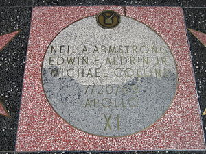 """Moon Landing monument, with square pink terrazzo surround (not the usual charcoal color), with light gray terrazzo Moon disk showing TV emblem at top and the brass lettering """"Neil A. Armstrong, Edwin E. Aldrin and Michael Collins, 7/20/69, Apollo XI"""""""