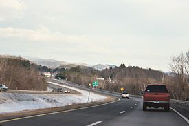 A four lane highway in snowy weather curving left with several cars on it. An exit sign and mountains are in the distance.