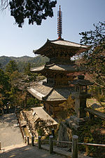 Three-storied wooden pagoda on a hillside.