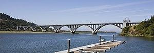Un grande fiume scorre sotto un ponte lungo elegante, con archi multipli.  Un bacino e barca sono in primo piano.