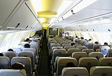 Cabin of the 767. There are seven seats per row, with two aisles separating the seats. Light shines through the side-wall windows and overhead lighting.