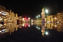 La place de Jaude de nuit et son reflet dans une fontaine