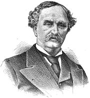 A man with dark, curly hair and a mustache wearing a dark jacket, vest, and tie and a white shirt