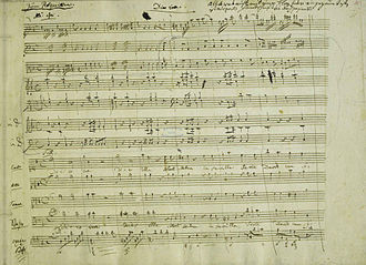 "Requiem (Mozart) - The beginning of the Dies irae in the autograph manuscript, with Eybler's orchestration. In the upper right, Nissen has left a note: ""All which is not enclosed by the quill is of Mozart's hand up to page 32."" The first violin, choir and figured bass are entirely Mozart's."