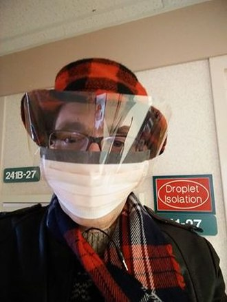 Surgical mask - A Kimberly-Clark procedure mask. Note the full facial shielding and the Droplet Isolation protocol signage.