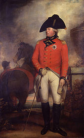 Clean-shaven man wearing the red jacket of an 1800 British army general with the star of the Order of the Garter, white breeches, black knee-high boots, and a black bicorne hat. Behind him a groom holds a horse.