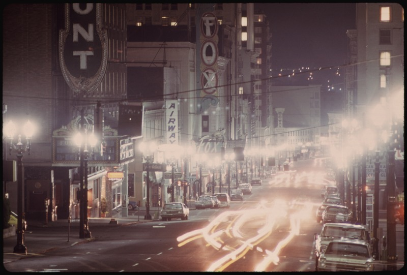LOOKING DOWN SOUTHWEST BROADWAY IN PORTLAND, DURING THE ENERGY CRISIS SHOWS LIMITED LIGHTING ON A MISTY EVENING - NARA - 555446