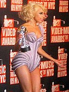 Right profile of a young blond woman. She wears a mauve leotard with purple stripes. Her hair is curled up behind her head. She holds a silver trophy in her right hand. A black background with red letters are visible behind her.
