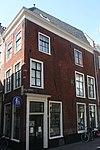 foto van Hoekhuis Lange Pieterskerkkoorsteeg. Twee gevelstenen met leeuwenmaskers en opschriften