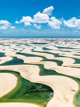 Photograph of the Lençóis Maranhenses National Park depicting fresh water collecting in the valleys between sand dunes, a layer of rock beneath the sand preventing the rain water from dissipating during the rainy season, thus resulting in a broad expanse of lagoons