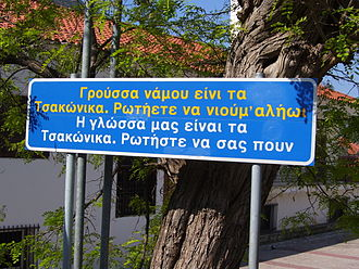 "Varieties of Modern Greek - (Tsakonian/Greek) ""Our language is Tsakonian. Ask and they'll tell you"". Greek sign in the town of Leonidio."