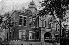A black and white photograph of a large brick building with two stories and a small dome