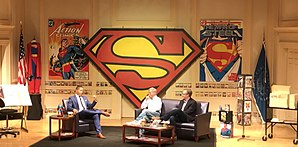 Three men seated onstage, flanked by Superman material