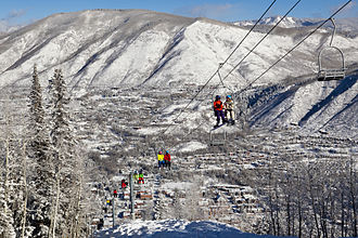 Aspen/Snowmass - Skiers and snowboarders ride up the iconic Lift 1A on Aspen Mountain with downtown Aspen in the background.