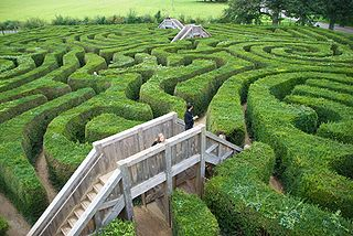 """outdoor garden maze or labyrinth in which the """"walls"""" or dividers between passages are made of vertical hedges"""