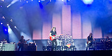 Five people. On the far left a person behind a console with a keyboard. Beside a person standing with semi-long hair, holding a bass guitar. Another person standing at the center, wearing black, holding a red guitar. To his right a person with long hair wearing black with a bass guitar in his hand. On the extreme right a person with a beret behind a drum kit.