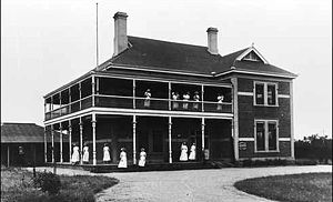 A large Federation style brick building with verandas and balconies, on which a dozen women in white are standing.