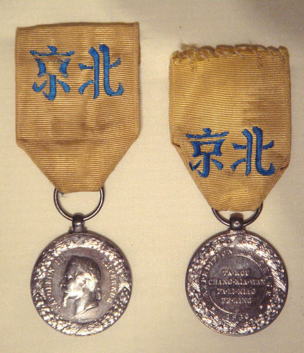 "French medal of the China Campaign (""Medaille de la Campagne de Chine""), 1861, in the Musee de la Legion d'Honneur. The Chinese characters inscribed on the ribbons read 'Beijing'. Medaille de la campagne de Chine 1861.jpg"