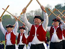 Men in bright red clothing holding sticks in the air.