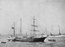 A three-masted ship with sails furled, short funnel amidships, flag flying from the stern on left of picture. Two small boats are close by, and a larger vessel decked with bunting is visible in the background.