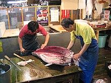Uso di un coltello oroshi hocho per sfilettare il tonno al mercato ittico di Tsukiji. La lama si curva lungo la linea della spina dorsale