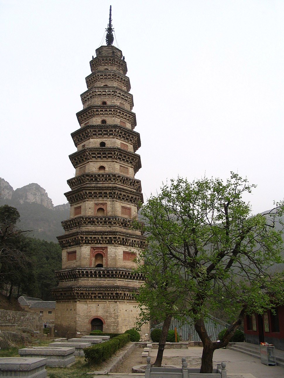 A thin, nine story tall octagonal pagoda. It is made of brown-orange brick and stone, and appears to lean slightly. Each floor is separated from the others by a double eave.
