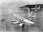 "Pan American Airways Sikorsky S-42 ""Pan American Clipper"" in flight over the under-construction San Francisco-Oakland Bay Bridge.jpg"