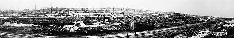 Panoramic view over traintracks to destroyed cityscape