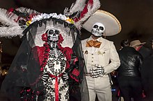 A man and woman in elaborate mariachi-style dress with skull paint