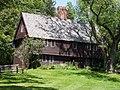 Tiu bruna kolonistila domo havas superpendadon dua etaĝo kaj ununuran centran kamentubon.