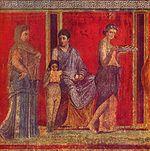 Mégalographie de la Villa des Mystères, Pompéi, vers -60.  Un jeune garçon lit un texte sous le regard de sa mère.