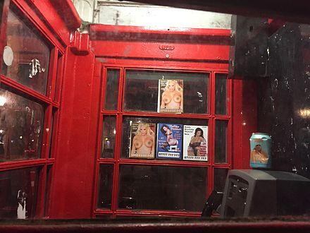 Advertenties van prostituees in een klassieke telefooncel tegenover het British Museum in Londen. Januari 2017