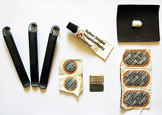 Puncture repair kit with tire levers, sandpaper to clean off an area of the inner tube around the puncture, a tube of rubber solution (vulcanizing fluid), round and oval patches, a metal grater and piece of chalk to make chalk powder (to dust over excess rubber solution). Kits often also include a wax crayon to mark the puncture location. Puncture-repaire-kit.jpg