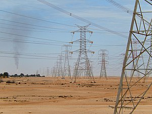 Energy in Qatar - Overhead power lines in Qatar. A gas flare of a refinery can be seen in the distance.