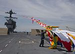 Quartermaster 1st Class Jose Triana attaches signal flags to a line (34285149176).jpg