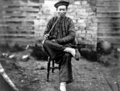 Queensland State Archives 1885 Chinese man in traditional dress seated with opium pipe Palmer Goldfields c1870.png