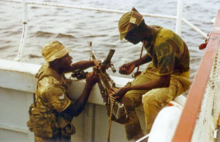 Two men in military fatigues handle a machine gun on the side of a boat