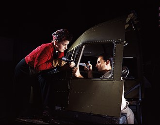 Rivet - Riveting team working on the cockpit shell of a C-47 transport at the plant of North American Aviation. The woman on the left operates an air hammer, while the man on the right holds a bucking bar