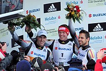 Three smiling men stand side-by-side in front of a crowd of photographers. Each holds up a flower bouquet with their right arm, and wears the same tight black-and-white jumpsuit with some yellow and red stripes. The man on the left wears a white cap, while the one in the middle wears a red headband.
