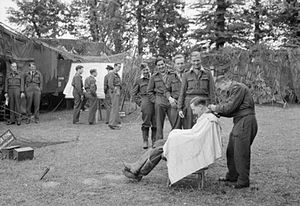 No. 65 Squadron RAF - Pilots line up for a haircut while waiting on standby near the No. 122 Wing Operations Room at Martragny, Normandy. In the chair is Flying Officer J. M. W. Lloyd of No. 65 Squadron RAF.
