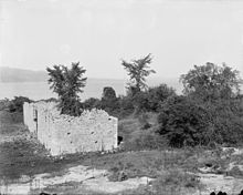 A black-and-white photograph. Ruined wall sections are visible in the center, with a tree growing out of the center of one of the structures. The lake is visible in the background, and hazy land is visible even further back.