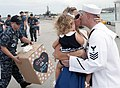 Sailor is greeted with the first kiss by his wife during a homecoming celebration USS Oklahoma City. (31360989422).jpg