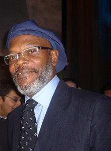 A middle-aged man, wearing a blue hat, glasses and a suit.