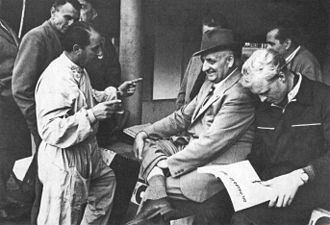 Enzo Ferrari - Entrepreneur Enzo Ferrari (center) in the box of the Monza Circuit in 1953 beside his driver Mike Hawthorn (right)