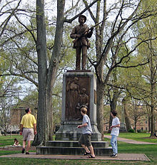 A statue of a soldier with three people walking around the base.