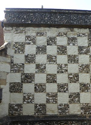Clunch - Flint and the pale stone, clunch used together in a checkerboard pattern on the wall of the side chapel at St Michael's Church, Mickleham, Surrey.
