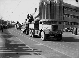 Queensland Brewery Ltd - Parade of military vehicles with the new headquarters in the background, July 1942
