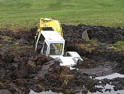 Photograph of a backhoe that is over fifty percent submerged in a large hole that it dug in a peat bog before falling in.