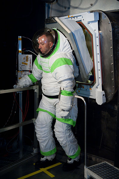 Suitport. Astronaut climbs into the spacsuit through the hatch. It does leak a small amount of air still, about a cubic foot. The spacsuit itself would also leak air constantly, all present day suits do, e.g. through flexible areas such as the joints.