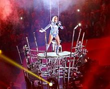 Lady Gaga standing atop a skeletal structure and singing, as red light is seen behind her.